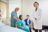 Portrait of mature male doctor explaining fetal heartbeat report to pregnant woman while nurse and m