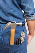 Extreme Close up of several tools in a man's rear denim pocket