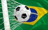 Brazil waving flag and soccer ball in goal net