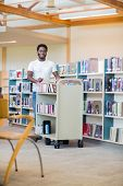 Portrait of African American librarian with trolley of books smiling in bookstore