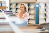 Mature female librarian working in library
