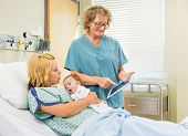 Mature female nurse explaining reports on digital tablet to woman with newborn babygirl in hospital