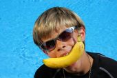 Boy With Banana Between His Teeth At Swimming Pool