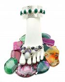 image of talisman  - Foot display form with anklet and toe jewelry surrounded by many colorful gemstone talismans - JPG