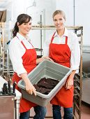 Portrait of beautiful workers carrying beef jerky in basket at butcher's shop