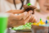 Closeup of woman's hand holding chocolate cupcake at birthday party