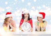christmas, x-mas, winter, happiness concept - three smiling women in santa helper hats with clock sh