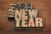Happy New Year 2014 greetings - text in vintage letterpress wood type blocks on a grunge wooden back