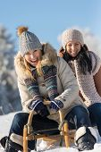 Two female friends sledge downhill in wintertime sunny snow day