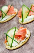 foto of canapes  - Canapes with smoked salmon cucumber and cream cheese selective focus closeup - JPG
