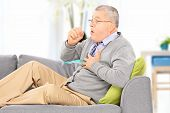 stock photo of cough  - Mature man seated on a sofa coughing because of pulmonary disease at home - JPG