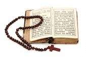 Old bible and rosary isolated on white background