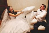 Portrait of happy newlywed couple fighting with pillows on sofa