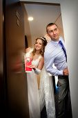 The newlyweds closing the door in hotel. Just married do not disturb sign
