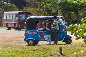 WELIGAMA, SRI LANKA - MARCH 7, 2014: Local people in tuk tuk vehicle. Tourism and fishing are two main business in this town.