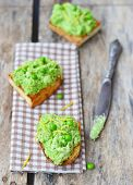 Bruschetta with green pea on a rustic background.