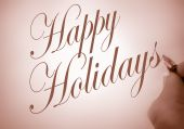 stock photo of happy holidays  - Person writing Happy Holidays in calligraphy script with sepia tone - JPG