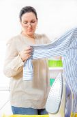 Cheerful housewife standing at the ironing board