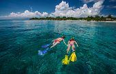 Two ladies snorkeling in tropical clear sea near the green island at sunny day. Gili Trawangan island, Indonesia