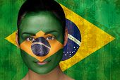 Composite image of beautiful football fan in face paint against brazil flag in grunge effect