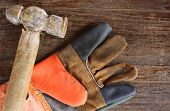 Old Hammer And Leather Gloves On Wood Background