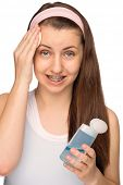 Girl with braces cleaning face with cotton pad isolated