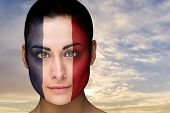 Composite image of beautiful brunette in france facepaint against scenic landscape with blue cloudy