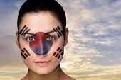 Composite image of beautiful brunette in south korea facepaint against scenic landscape with blue cl