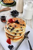 High angle shot of a stack of fresh homemade blueberry pancakes. The plate is on a rustic farmhouse
