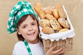 Happy baker boy holding basket with fresh bakery products - closeup