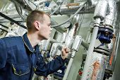 picture of manometer  - repairman engineer or inspector of fire engineering system or heating system with valve equipment in a boiler house - JPG