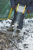 Builder worker with pneumatic jack hammer drill equipment breaking asphalt at construction road work