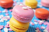 some appetizing macarons with different colors and flavors on a blue background