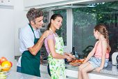 couple girl, father mother and daughter cooking