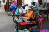 MAEKLONG, THAILAND - MARCH 24: Tailor repairing clothes on March 24, 2014 in famous Maeklong Railway Market also known as Talad Rom Hub or Umbrella Pulldown Market