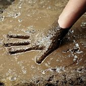 Person playind in mud with hand being creative
