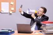 Angry businessman in an office, shouting on a megaphone, holding a phone in the hand