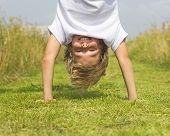 A boy stands upside down in the summer grass.