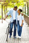 lovely african couple walking with a bike outdoors