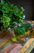 stock photo of helleborus  - Mint tea with lime on the old wooden table