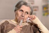 Elderly woman making inhalation