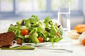 Closeup photo of healthy fresh salad with a slice of rye-bread placed on white tabletop.
