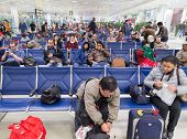 DOHA, QATAR - FEBRUARY 18, 2014: People waiting for their flight at Doha International Airport, the