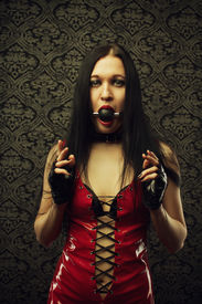 image of sado-masochism  - Pretty girl in red latex dress with mouth gag stands in an empty room - JPG
