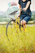 Young woman with bicycle in meadow