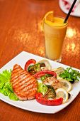 Tasty dish of salmon steak with vegetables and juice