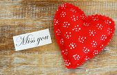 Miss you card with red heart on rustic wooden surface