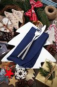 Christmas table place setting with christmas decorations on wooden table