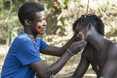 Hamar Men Paint Each Other's Face In A Preparation To A Bull Jumping Ceremony.