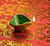 An illuminated, decorative Diwali lamp against glittering background